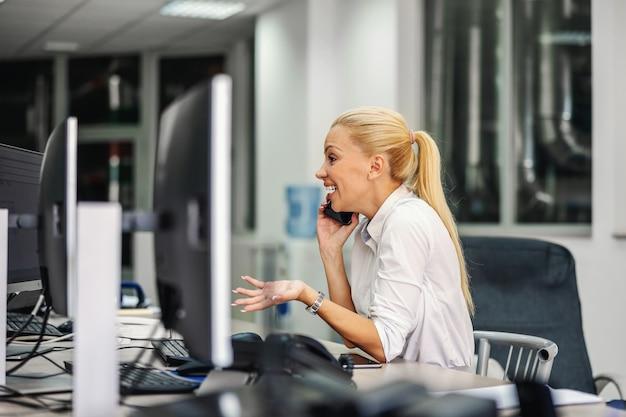 Geschäftsfrau, die im kontrollraum im heizwerk sitzt und telefongespräch mit ihrem chef hat