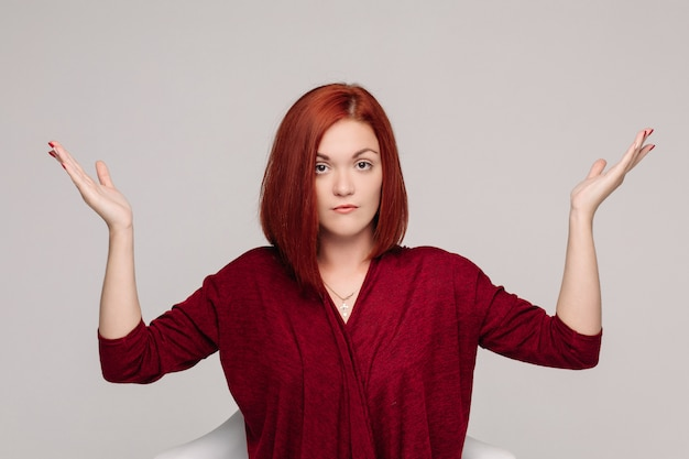 Geschäftsfrau, die im rot hat passives gefühl trägt und frustriert schaut.