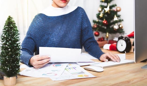 Geschäftsfrau, die im weihnachtsfeiertag im büro mit weihnachtsdekoration auf tabelle arbeitet