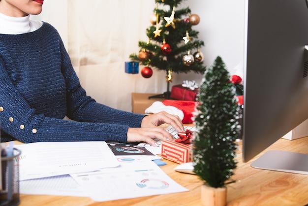 Geschäftsfrau, die im weihnachtsfeiertag im büro mit weihnachtsdekoration auf tabelle arbeitet.
