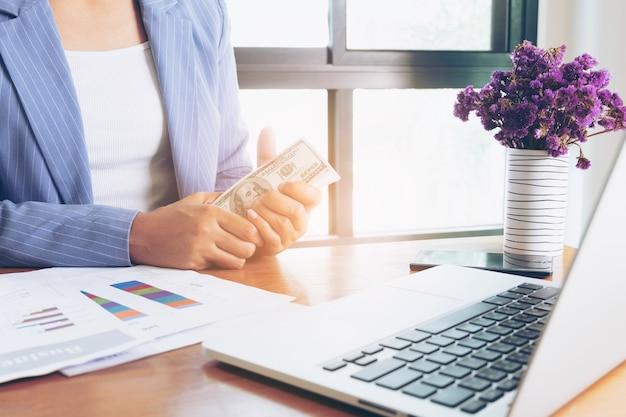 Geschäftsfrau, die in der hand dollar-banknote im büro hält
