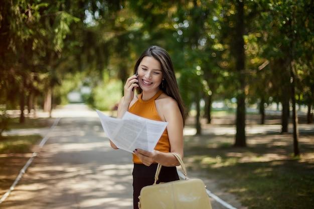 Geschäftsfrau, die in der hand in den park spricht am telefon mit dokumenten geht. glück und lachen. gute nachrichten
