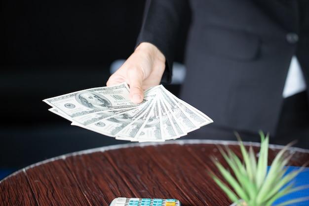 Geschäftsfrau, die in der hand us-dollar geld hält. usa-rechnungen im anlagekonzept.