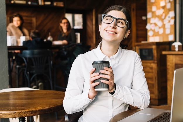 Geschäftsfrau, die in der kaffeestube träumt