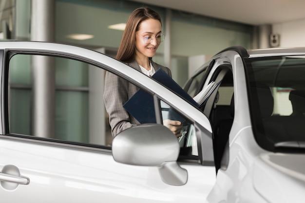 Geschäftsfrau, die in ein auto einsteigt