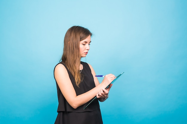 Geschäftsfrau, die in eine zwischenablage schreibt, lokalisiert auf einem blauen hintergrund.