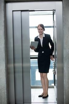 Geschäftsfrau, die in einem aufzug steht, der eine digitale tablette hält