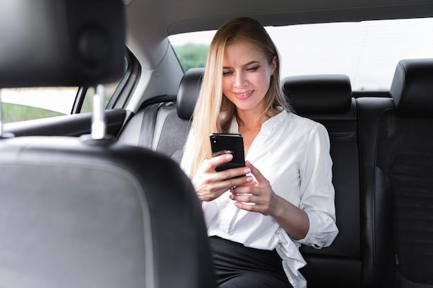 Geschäftsfrau, die in einem auto sitzt und das telefon betrachtet