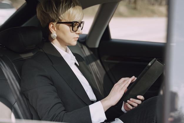 Geschäftsfrau, die in einem auto sitzt und eine tablette benutzt