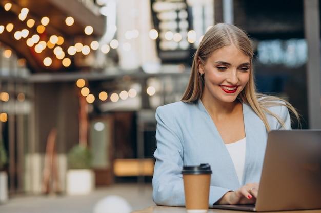 Geschäftsfrau, die in einem café am computer arbeitet und kaffee trinkt