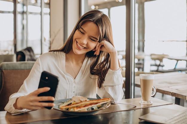 Geschäftsfrau, die in einem café zu mittag isst und am computer arbeitet
