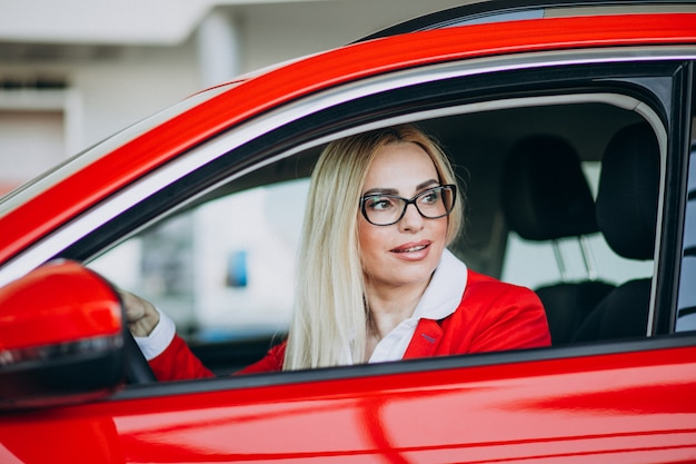 Geschäftsfrau, die in einem neuen auto in einem autoausstellungsraum sitzt