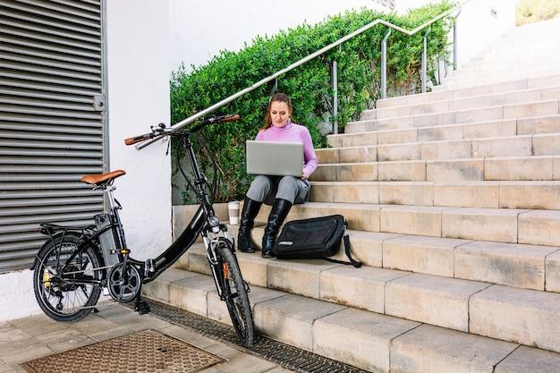 Geschäftsfrau, die in einem park mit ihrem elektrischen fahrrad, laptop und handy sitzt.