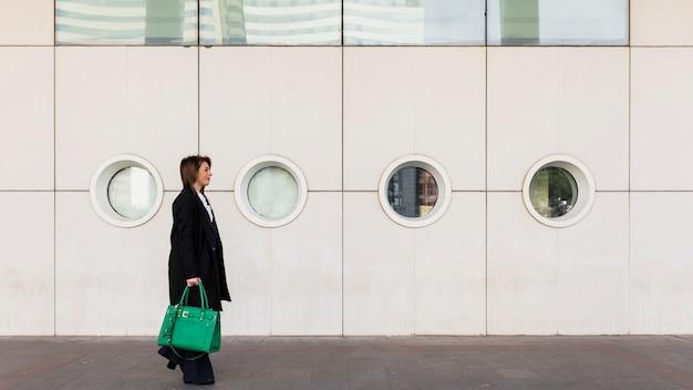 Geschäftsfrau, die in straße mit grüner tasche geht