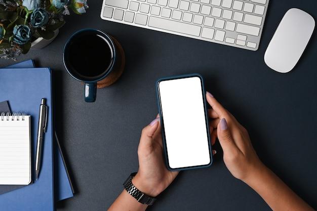 Geschäftsfrau, die intelligentes telefon auf schwarzem hintergrund verwendet.