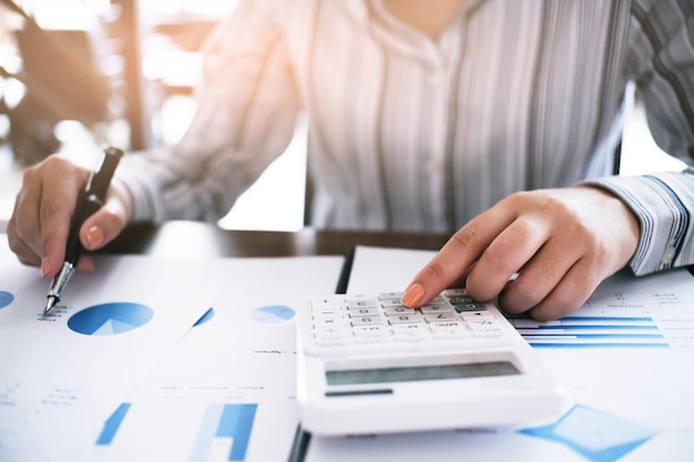 Geschäftsfrau, die investitionsdiagramme analysiert und taschenrechner drückt