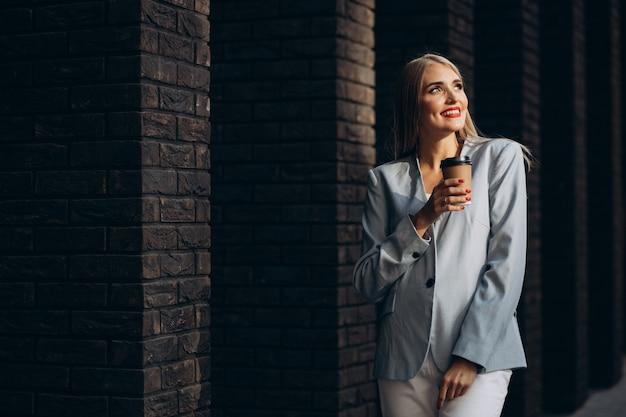 Geschäftsfrau, die kaffee am bürozentrum trinkt