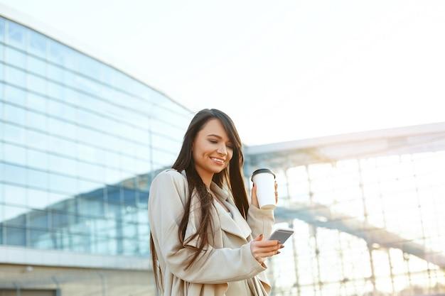 Geschäftsfrau, die kaffee hält und telefon nahe büro verwendet. porträt der schönen lächelnden frau mit telefon, im freien stehend. telefonische kommunikation.