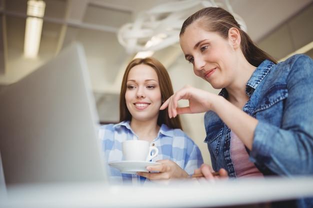 Geschäftsfrau, die kaffeetasse beim arbeiten mit kollegebüro hält