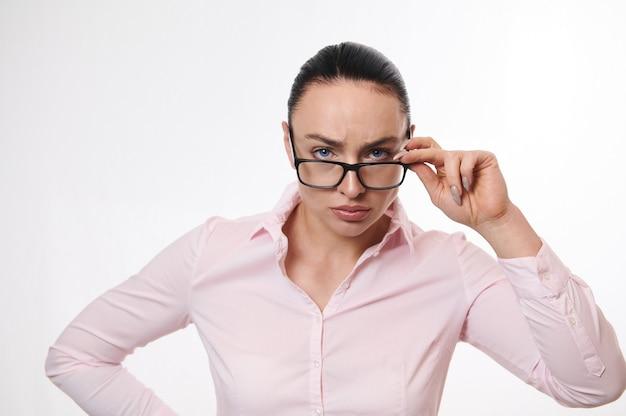 Geschäftsfrau, die kamera durch gesenkte brille betrachtet. isoliertes porträt auf weißem hintergrund mit kopienraum