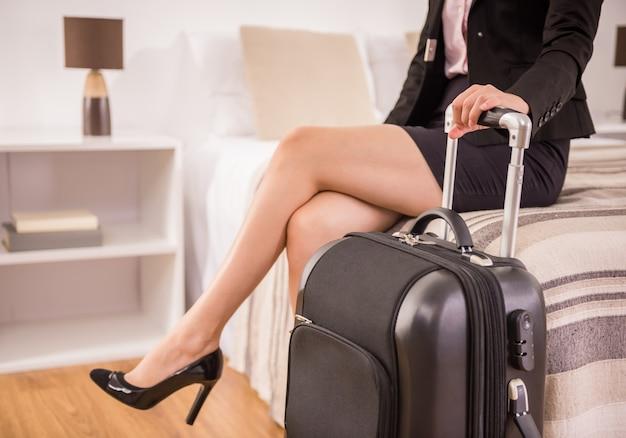 Geschäftsfrau, die koffer beim sitzen auf bett hält.