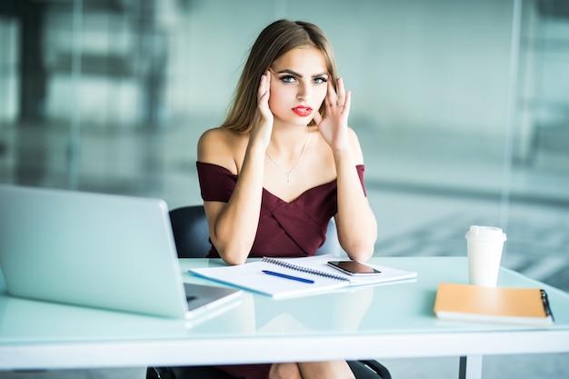 Geschäftsfrau, die kopfschmerzen bei der arbeit unter verwendung eines desktop-computers im büro leidet