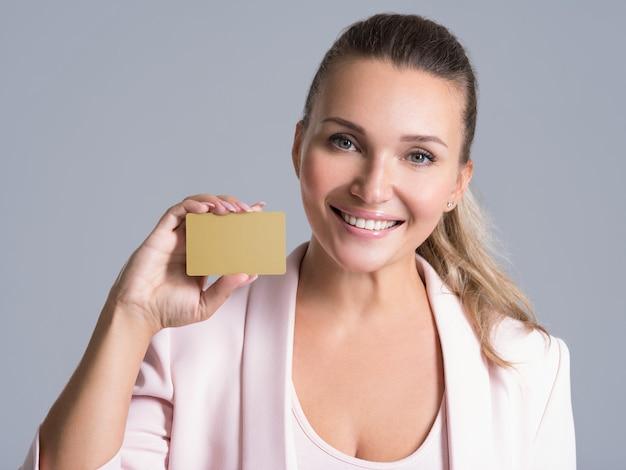 Geschäftsfrau, die kreditkarte gegen ihr gesicht lokalisiertes studioporträt hält
