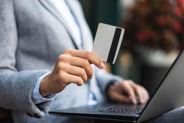Geschäftsfrau, die kreditkarte hält, während laptop verwendet wird
