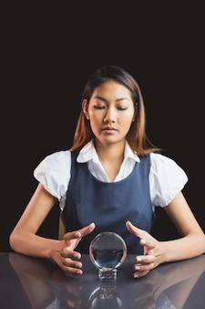 Geschäftsfrau, die kristallkugel auf schwarzem hintergrund verwendet