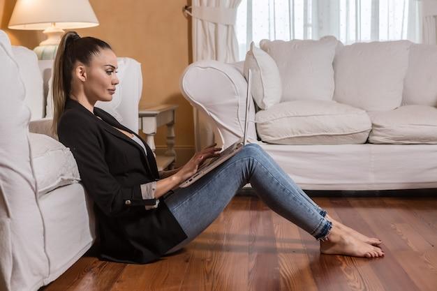 Geschäftsfrau, die laptop auf boden des hotelzimmers verwendet