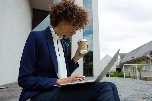 Geschäftsfrau, die laptop beim kaffee in der nähe des bürogebäudes verwendet