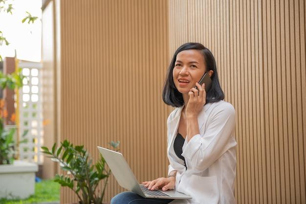 Geschäftsfrau, die laptop-computer benutzt und mit handy spricht