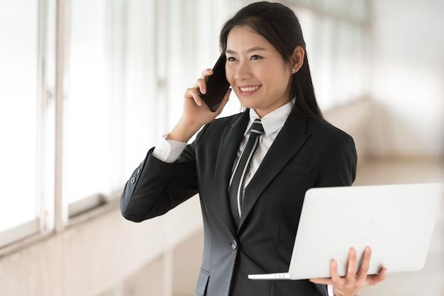 Geschäftsfrau, die laptop hält und auf smartphone spricht.