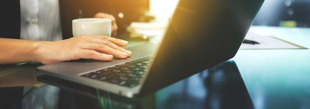 Geschäftsfrau, die laptop-touchpad beim kaffeetrinken im büro benutzt und berührt