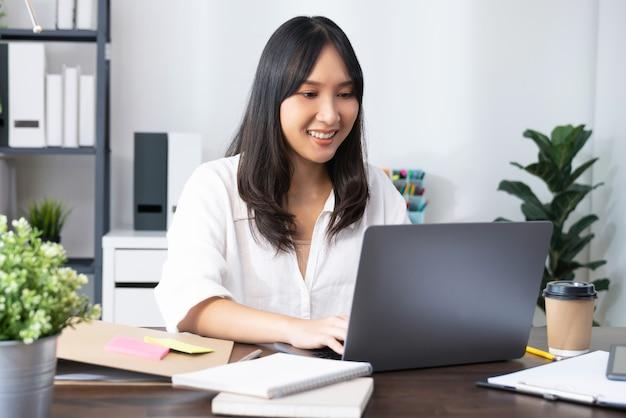 Geschäftsfrau, die laptop verwendet und am tisch im innenministerium sitzt.