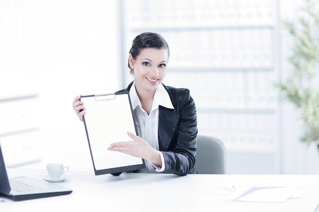 Geschäftsfrau, die leeres blatt zeigt und an ihrem schreibtisch sitzt. foto mit kopienraum