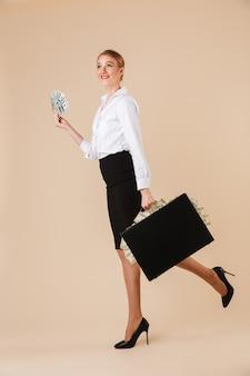 Geschäftsfrau, die lokal gehenden koffer mit geld geht.