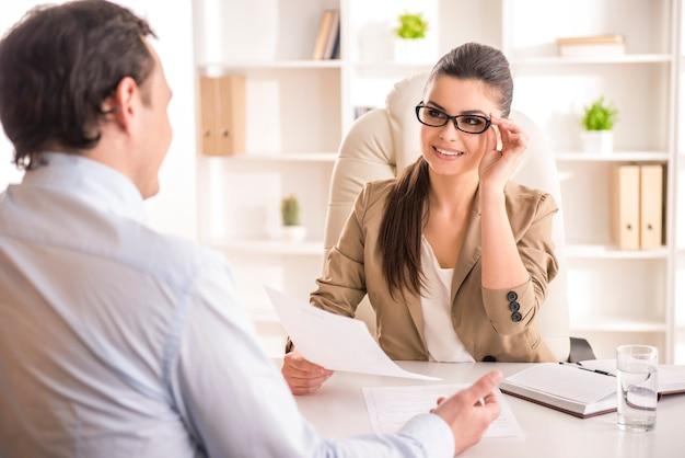 Geschäftsfrau, die männlichen kandidaten für job im büro interviewt.