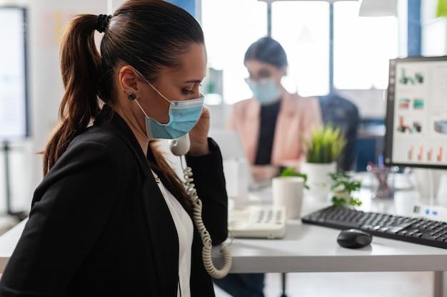 Geschäftsfrau, die marketingstrategie mit manager bespricht, die festnetz-planungsmarketing-präsentation verwendet, die im büro arbeitet. unternehmerfrau mit medizinischer gesichtsmaske zur vorbeugung einer infektion mit covid19