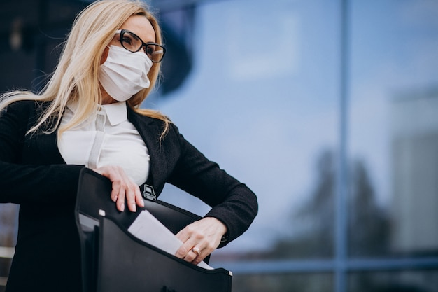 Geschäftsfrau, die maske außerhalb des geschäftszentrums trägt