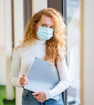 Geschäftsfrau, die medizinische maske trägt und dokumente hält