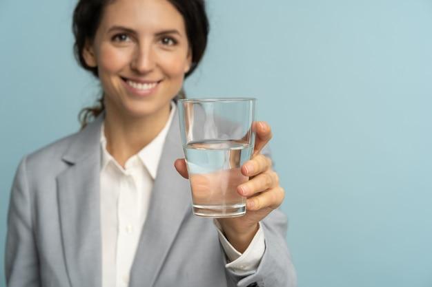 Geschäftsfrau, die mineralwasserglas hält, erinnert daran, nicht zu vergessen, wasser bei der arbeit zu trinken