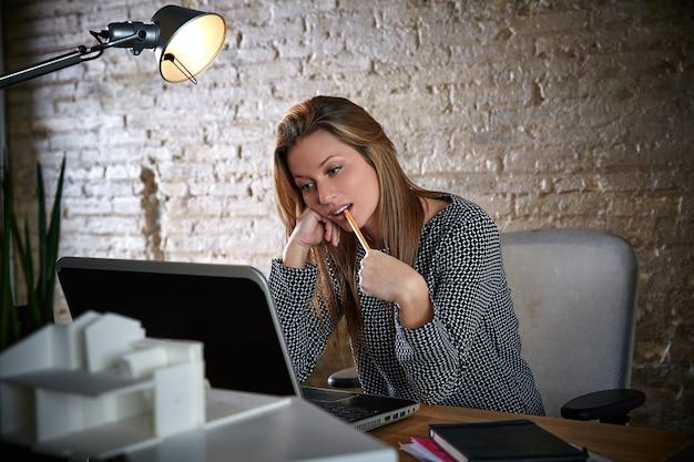 Geschäftsfrau, die mit bleistift im mund denkt