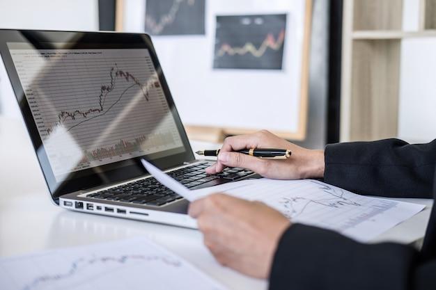 Geschäftsfrau, die mit computer, laptop arbeitet, börsehandel des diagramms bespricht und analysiert