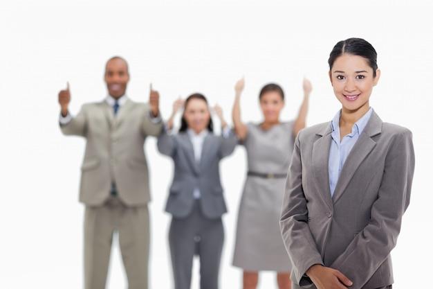 Geschäftsfrau, die mit den mitarbeitern genehmigen im hintergrund lächelt