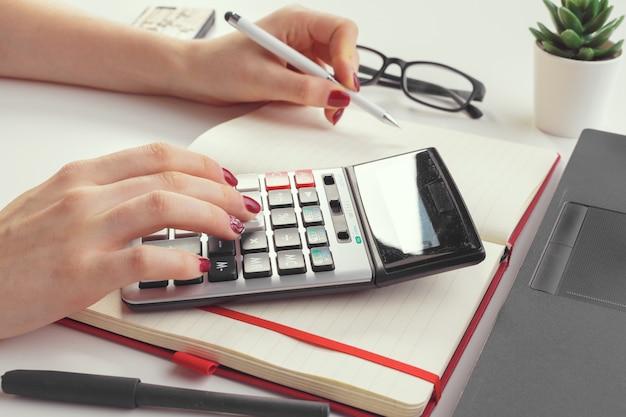 Geschäftsfrau, die mit der finanzdatenhand unter verwendung des taschenrechners arbeitet