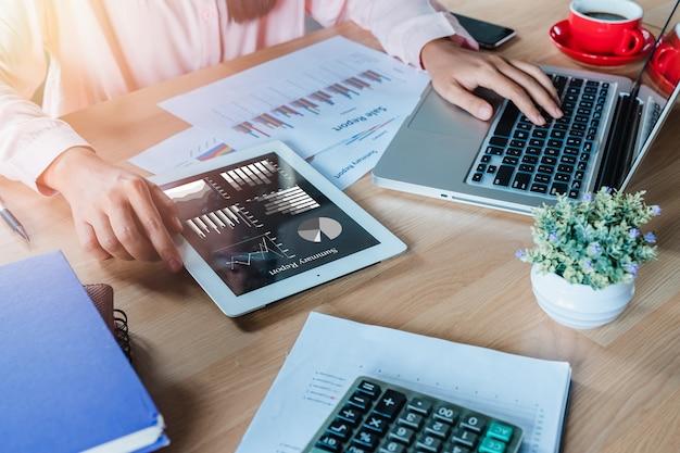Geschäftsfrau, die mit digitaler tablette und buch und dokument auf hölzernem schreibtisch in modernem arbeitet