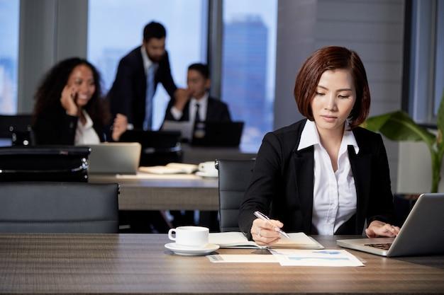 Geschäftsfrau, die mit dokument im büro arbeitet