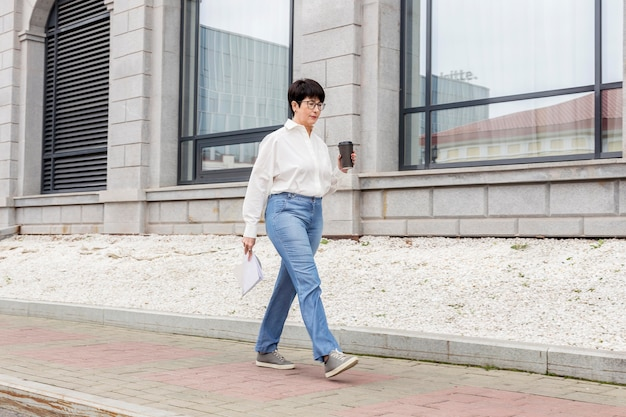 Geschäftsfrau, die mit einem kaffee in ihrer hand geht