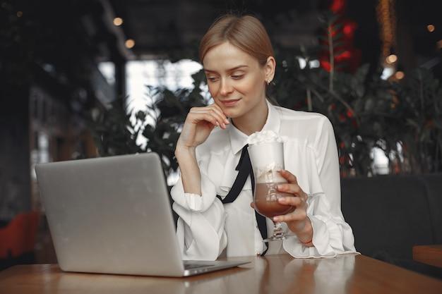Geschäftsfrau, die mit einem laptop am tisch sitzt